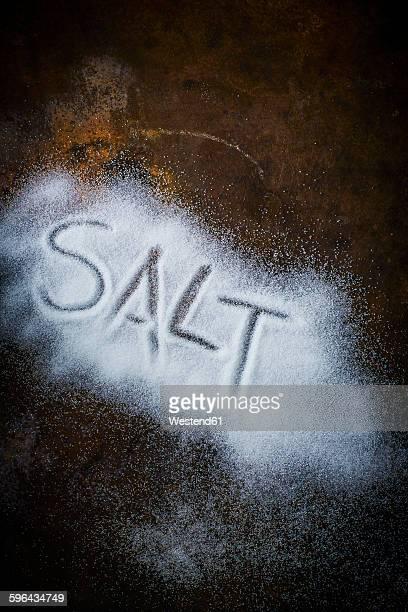 The word salt written in salt on rusty metal