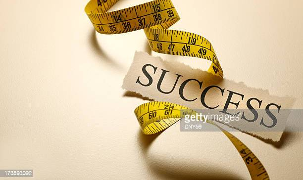 The word success on top of coiled tape measure