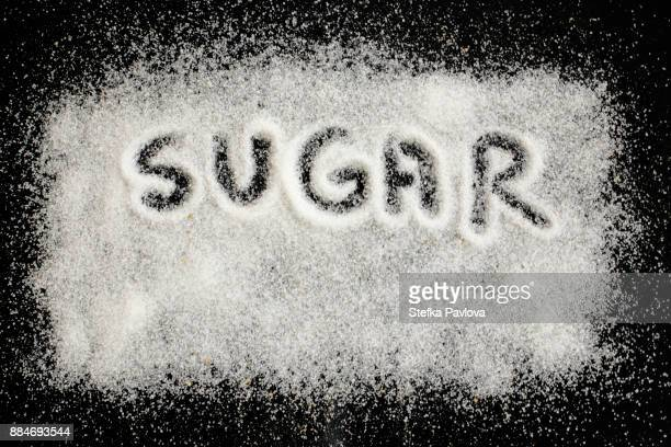 the word sugar written on sugar background on black