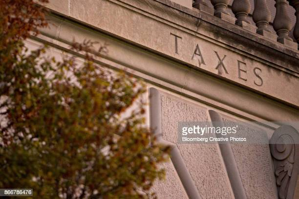 """the word """"taxes"""" is seen on the facade of the internal revenue service (irs) headquarters - irs stock photos and pictures"""