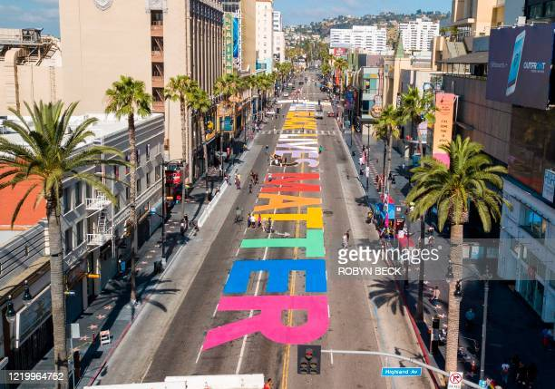 The words All Black Lives Matter are seen painted on Hollywood Blvd before the start a solidarity march between the LGBTQ and Black Lives Matter...