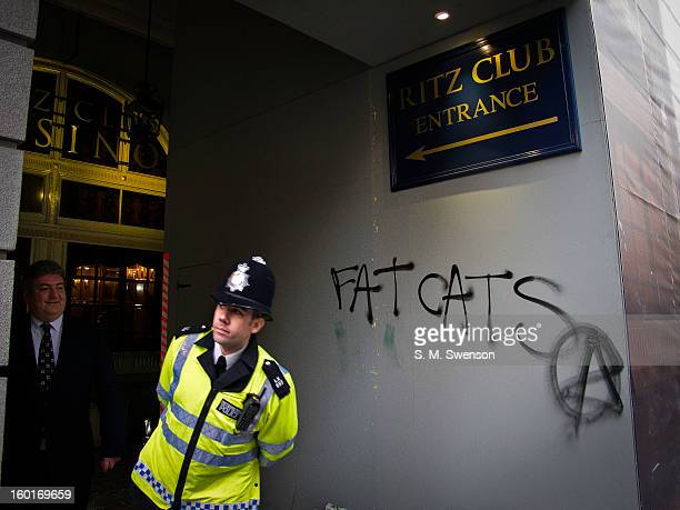The words 'Fat Cats' with an anarchy symbol are spray painted outside one of London's most luxurious hotel, The Ritz in Mayfair. A policeman peers...