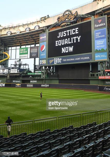 """The words """"Justice Equality Now"""" are displayed on the jumbotron behind two members of the Milwaukee Brewers as they play catch in Black Lives Matter..."""