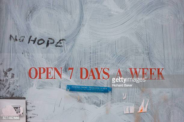 The words 'Open seven days a week' and 'No hope' written on a closed business in Camden North London England Around a recessionbled Britain...