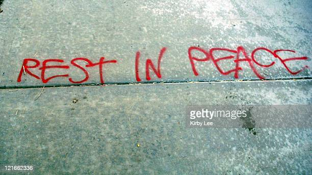 The words Rest in Peace in red spray paint on a sidewalk in front of makeshift memorial for USC kicker Mario Danelo at Point Fermin Park in San Pedro...