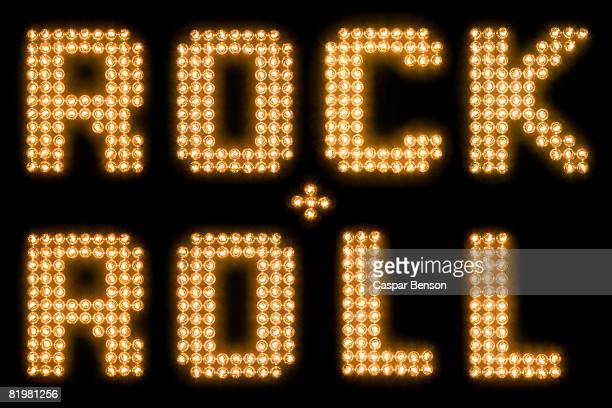 The words rock and roll in illuminated light bulbs