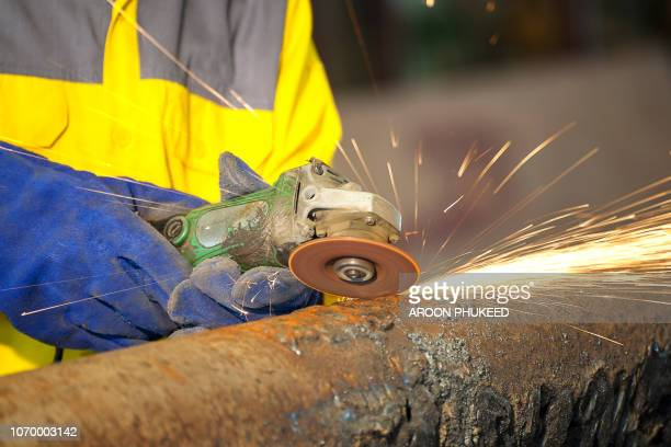 the worker grinding metal - fabricage apparatuur stock pictures, royalty-free photos & images