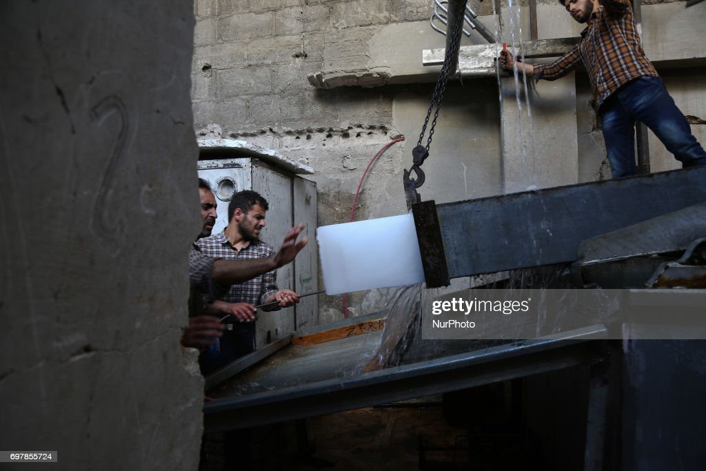 The worker holds the ice cube after finishing the manufacturing in Douma of Damascus, Syria, on 19 June 2017.
