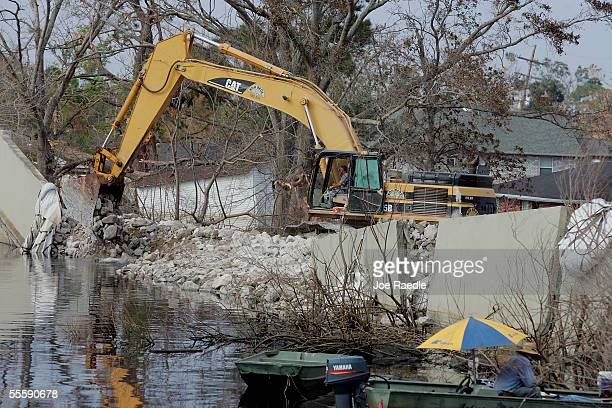 The workers dump rocks into a pile with the help of a crane as they work on patching the London Canal levee which broke when the Hurricane Katrina...