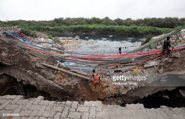 The workers of private agencies removing fiber cable wire which are burden under the collapse bridge which was caved in on saturday near Mahim T...