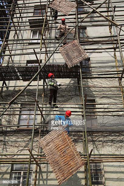 The workers put up the scaffold for repairing residents' houses near the construction of the China Pavilion at the World Expo site on April 21 2009...