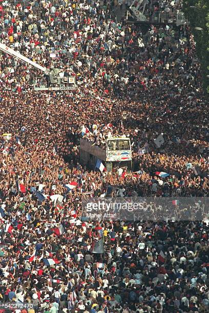 The world champion are driven up the Champs Elysees among a human sea of supporters.