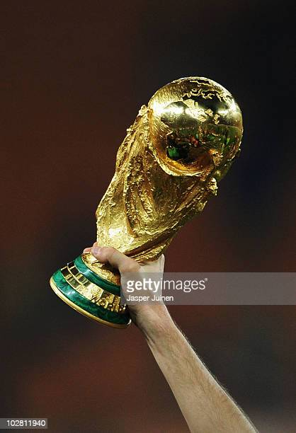 The World Cup trophy is held aloft as the Spain team celebrate victory following the 2010 FIFA World Cup South Africa Final match between Netherlands...