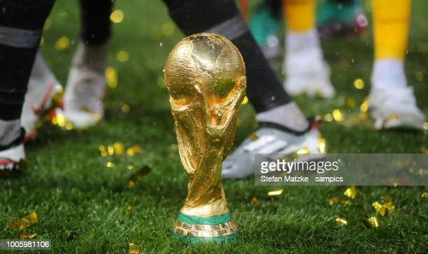 The World Cup trophy is seen on the pitch surrounded by ticker tape after the 2018 FIFA World Cup Russia Final between France and Croatia at Luzhniki...