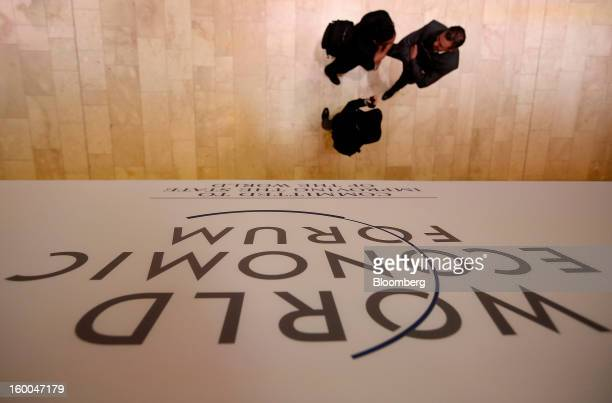 The World Economic Forum logo is displayed over attendees speaking in the main hall on day three in Davos Switzerland on Friday Jan 25 2013 World...