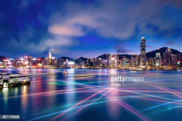 the world famous night scene of hong kong city skyline with busy water traffic navigate across victoria harbour - hong kong fotografías e imágenes de stock