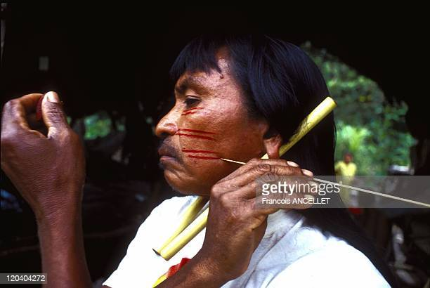 The world of Jivaro Indian in Ecuador in 1993 Pinientsa paints his face with Achiote red