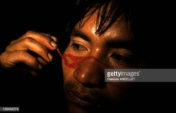 The world of Jivaro Indians in Ecuador in 1993 Indian from the Shuar ethnic group painting himself with Achiote red Rio Morona Ecuadorian Amazon