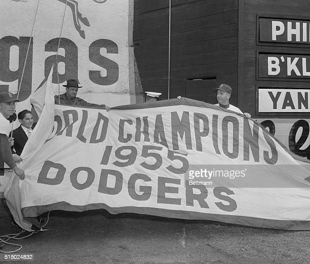 The World Series flag is proudly raised over Ebbets Field as a feature of the opening day ceremony as the Dodgers played host to the Phillies today...