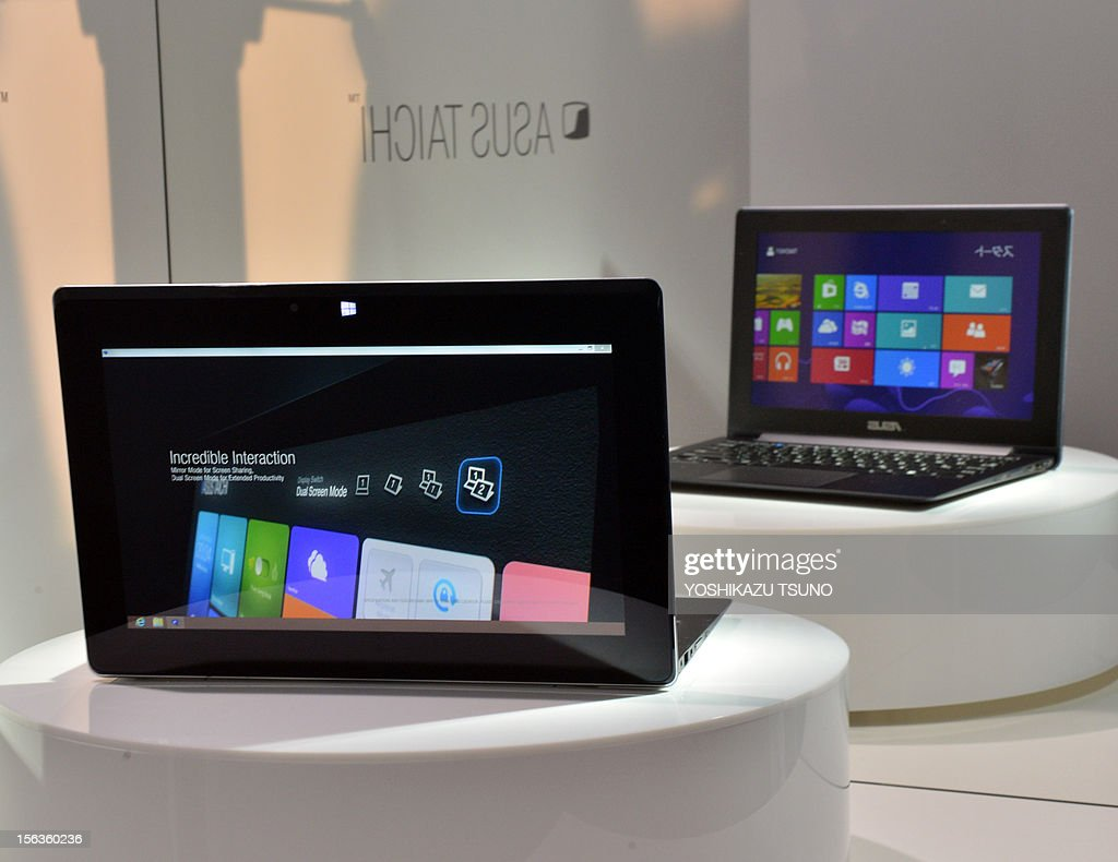 The world's first dual screens notebook computer 'Taichi', produced by Taiwan's personal computer giant ASUS and which has 11.6-inch LCD display on the both side, enabling to use as a tablet and notebook computer, is displyed in Tokyo on November 14, 2012, at (R) is reflected image on a miror. The unique PC, equipped with Intel's Core i7 processor on its CPU will go on sale December 8. AFP PHOTO / Yoshikazu TSUNO