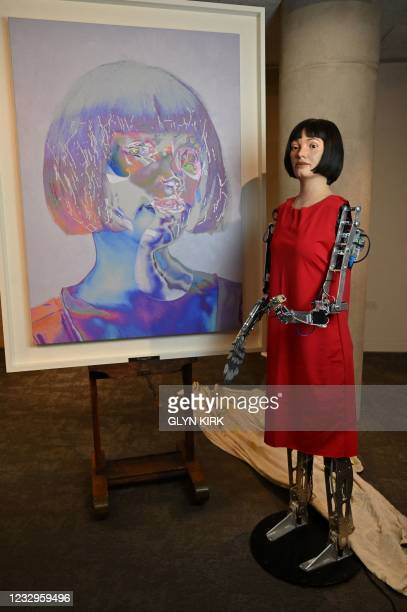 The worlds first ultra-realistic AI robot artist, Ai-Da, who can draw, paint and is a performance artist, is pictured alongside her self-portrait...