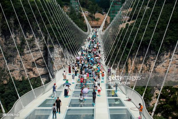 TOPSHOT The world's highest and longest glassbottomed bridge is seen above a valley in Zhangjiajie in China's Hunan Province on August 20 2016 / AFP...