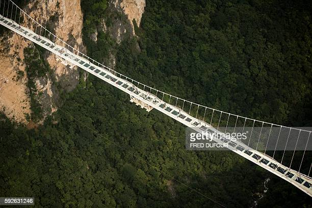 The world's highest and longest glass-bottomed bridge is seen above a valley in Zhangjiajie in China's Hunan Province on August 21, 2016. / AFP /...