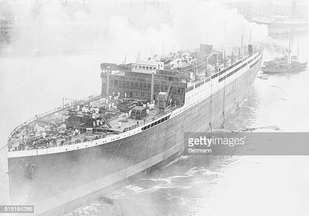 The world's largest motorship, the Britannic, in charge of tugs after it was launched, at ship yards here. It is the pioneer motorship of the White...
