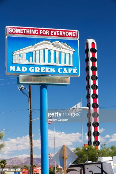 the world's largest thermometer in baker, gateway to death valey, reading 102 degree fahrenheit, california, usa, with a sign for the mad greek cafe. - カリフォルニア州ベーカー ストックフォトと画像