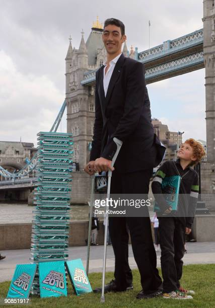 The worlds new tallest man Sultan Kosen 26 of Turkey poses with Josh Henderson 10 in front of Tower Bridge to celebrate the launch of the 2010...