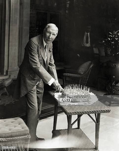 The world's richest man John D Rockefeller photographed in his Pocantico Hills home on his 90th birthday He is cutting his birthday cake