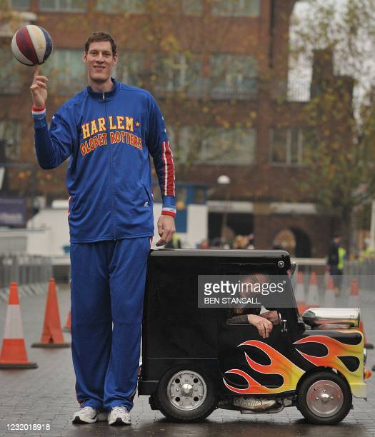 The world's tallest Basketball player, British man Paul 'Tiny' Sturgess , measuring 231.8cm high poses in front of the British inventor of the...