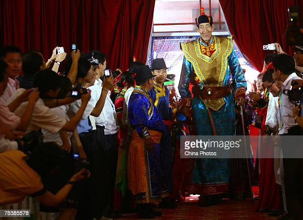 The world's tallest man Bao Xishun walks in to attend his traditional Mongolian wedding ceremony with his bride Xia Shujuan at Genghis Khan's...