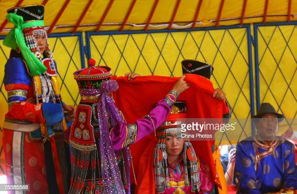 The world's tallest man Bao Xishun's bride Xia Shujuan wears a red scarf during their traditional Mongolian wedding ceremony at Genghis Khan's...