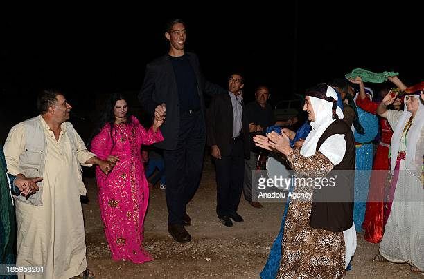 The World's tallest man Sultan Kosen and his fiancee Merve Dibo dance the halay a Turkish national dance during their henna night the ceremony held...