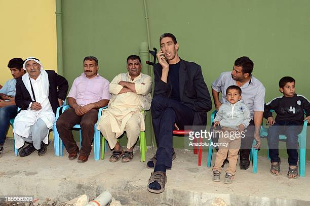 The World's tallest man Sultan Kosen sits with relatives during his henna night the ceremony held one day before the wedding on October 26 2013 in...