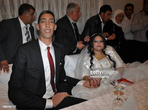 The World's tallest man Sultan Kosen whose height is measured at 2 meters 51 centimeters poses with Merve Dibo during their wedding ceremony on...