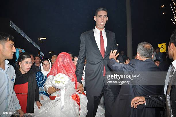The World's tallest man Sultan Kosen whose height is measured at 2 meters 51 centimeters walks with Merve Dibo for their wedding ceremony on October...