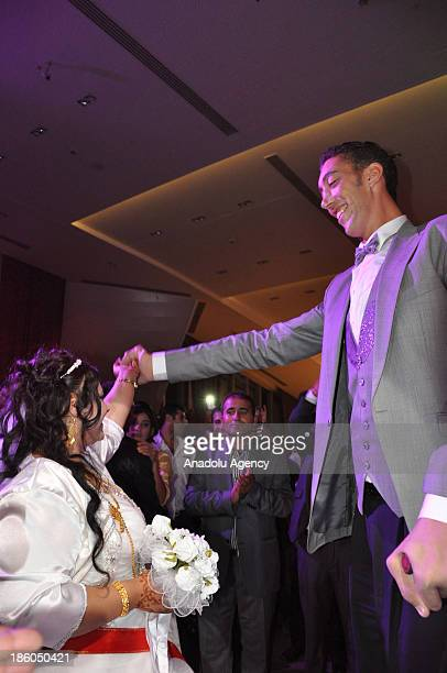 The World's tallest man Sultan Kosen whose height is measured at 2 meters 51 centimeters dances with Merve Dibo during their wedding ceremony on...