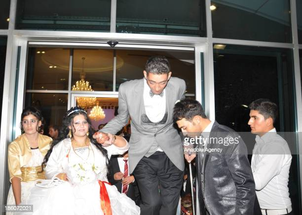 The World's tallest man Sultan Kosen whose height is measured at 2 meters 51 centimeters walks with Merve Dibo during their wedding ceremony on...