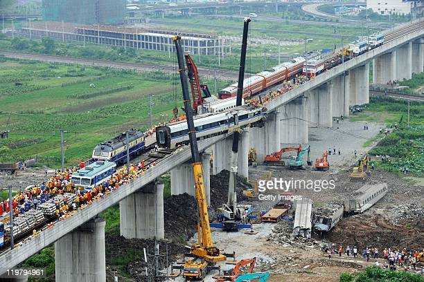 The wreckage of a carriage is lifted from the accident scene of the crash caused by the collision of two trains on July 24 2011 in Wenzhou Zhejiang...