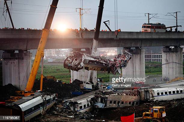 The wreckage of a carriage is lifted from the accident scene of the crash caused by the earlier collision of two trains on July 24 2011 in Wenzhou...