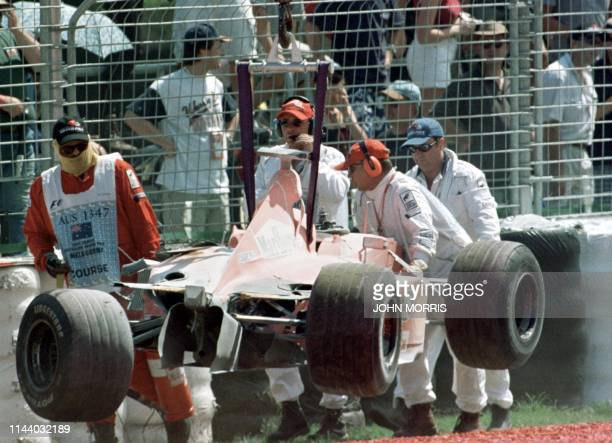 The wreckage of Michael Schumacher's Ferrari is removed from the track after he crashed during the second practice session at the Australian Formula...