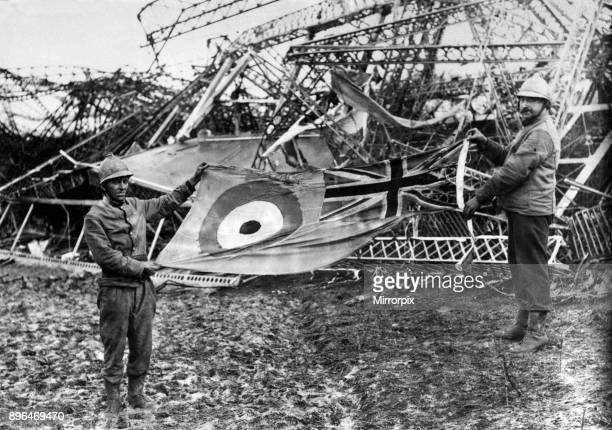 The wreckage of the R101 airship which crashed at AAllonne Beauvais near Paris France Firemen holding up the scorched ensign which was found flying...