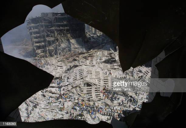 The wreckage of the World Trade Center is visible through the broken window of an apartment building near the wreckage September 13, 2001 in New York...