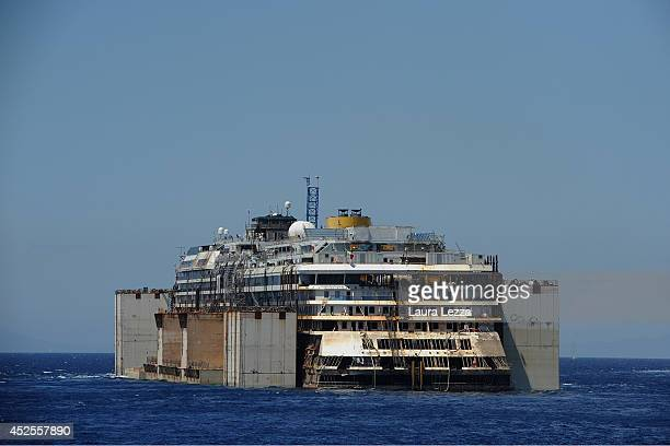 The wrecked cruise ship Costa Concordia is towed by tugs from Giglio into the open sea after being refloated on July 23 2014 in Isola del Giglio...