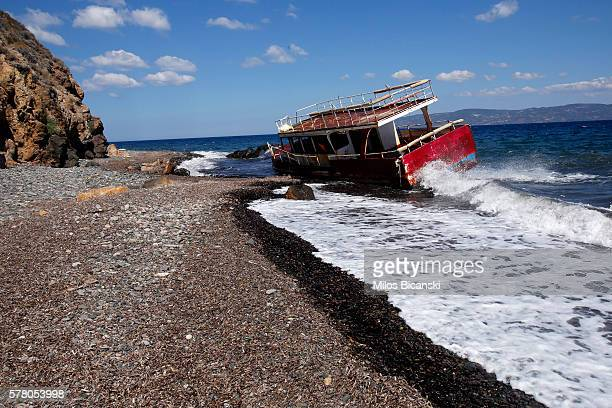 The wrecked remains of a ship lie on the shore on the beach of Skala Kaminas which was used by refugees to cross Aegean sea from Turkey to Greece...