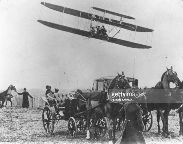 The Wright brothers' flying machine in flight at Pau France piloted by Wilbur Wright with passenger and team member Paul Tissandier 1909
