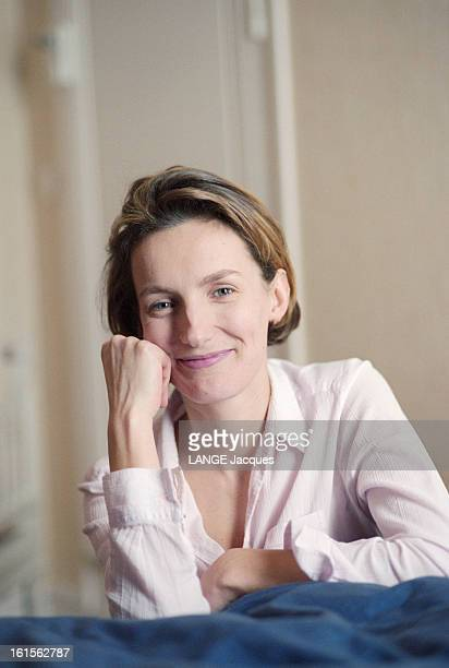 The Writer Anna Gavalda L'écrivain Anna GAVALDA souriante de face le poing contre sa joue chez elle à Melun