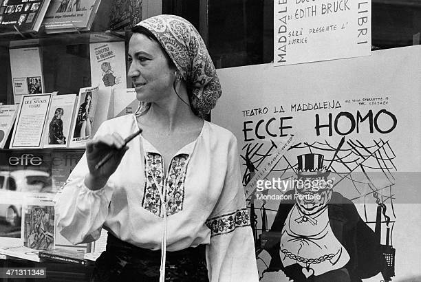 The writer Barbara Alberti wears a scarf and smokes a long cigarette close to the poster of her theatre work Ecce Homo Rome 1974